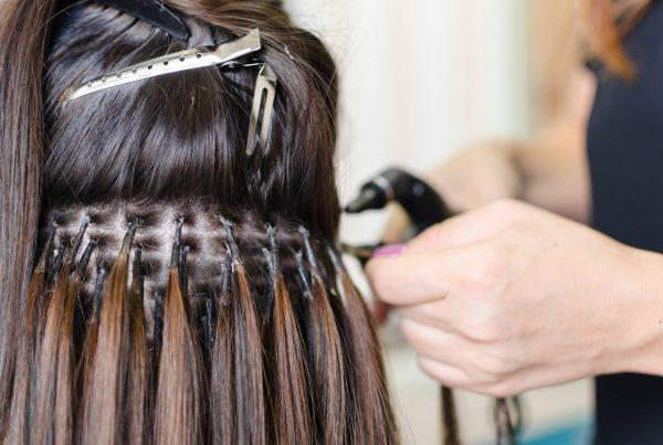 stylist putting in Keratin Bonded Hair Extensions