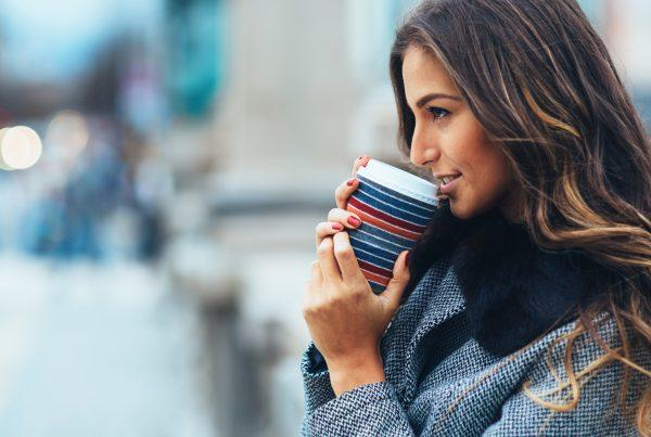 woman drinking coffee after a salon appointment to color her hair with trendy fall hair colors