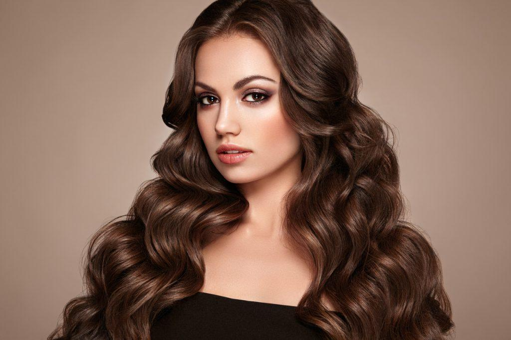 Woman with long brown keratin bonded hair extensions in Denver